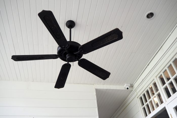 Black wood and wicker remote controlled ceiling fan mounted on thin white shiplap ceiling